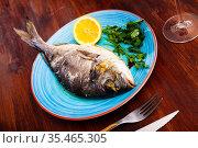 Baked in oven dorado fish with orange on plate. Стоковое фото, фотограф Яков Филимонов / Фотобанк Лори