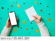 Woman's hands with paper notebook and smartphone,writing notes. Setting... Стоковое фото, фотограф Zoonar.com/OKSANA SHUFRYCH / easy Fotostock / Фотобанк Лори