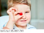Kleiner Junge hält einen roten Bonbon in einer Hand. Стоковое фото, фотограф Zoonar.com/Robert Kneschke / age Fotostock / Фотобанк Лори