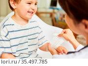 Kinderarzt bindet Mullbinde um das verletzte Handgelenk von Kind ... Стоковое фото, фотограф Zoonar.com/Robert Kneschke / age Fotostock / Фотобанк Лори