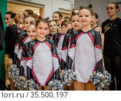 Moscow, Russia - December 22, 2019: Young girls sports team awaits start of performance at cheerleader competition. Редакционное фото, фотограф Андрей Копылов / Фотобанк Лори