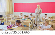 Young female teacher standing at whiteboard in classroom, conducting lesson with preteen pupils. Стоковое видео, видеограф Яков Филимонов / Фотобанк Лори