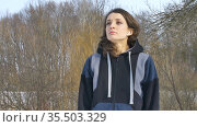 Early spring portrait of young athletic girl doing exercise in the morning in the park wearing dark sportwear. Healthy lifestyle concept. Стоковое видео, видеограф Ольга Балынская / Фотобанк Лори