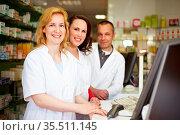 Drei lächelnde Apotheker stehen hinter der Theke. Стоковое фото, фотограф Zoonar.com/Robert Kneschke / age Fotostock / Фотобанк Лори