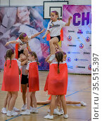 Moscow, Russia - December 22, 2019: Little european girls of school age perform at cheerleading competitions, show trick. Редакционное фото, фотограф Андрей Копылов / Фотобанк Лори