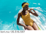 African american woman in swimming pool sunbathing on inflatable. Стоковое фото, агентство Wavebreak Media / Фотобанк Лори