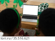 African american couple wearing st patrick's day costumes making a video call. Стоковое фото, агентство Wavebreak Media / Фотобанк Лори