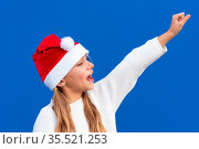 Joyful Young girl in Santa hat gesturing on blue background. High... Стоковое фото, фотограф Zoonar.com/DAVID HERRAEZ CALZADA / easy Fotostock / Фотобанк Лори