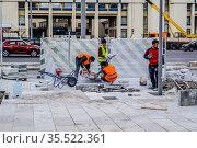 Рабочие-мигранты  укладывают тротуарную плитку на Зубовском бульваре в городе Москве с помощью строительной техники (2017 год). Редакционное фото, фотограф Владимир Устенко / Фотобанк Лори
