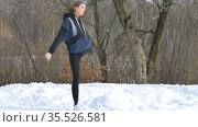 Ukraine, Lviv, February 21, 2021 - Early spring portrait of young athletic girl doing exercise in the morning in the park wearing dark sportwear. Healthy lifestyle concept. Редакционное видео, видеограф Ольга Балынская / Фотобанк Лори