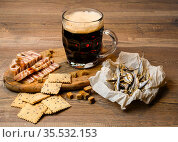 A glass of dark beer with a small amount of foam on a wooden table with dried fish, salted cookies, dried meat and crackers. Стоковое фото, фотограф Сергей Фролов / Фотобанк Лори