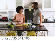 Happy diverse couple in kitchen smiling and making health drink. Стоковое фото, агентство Wavebreak Media / Фотобанк Лори