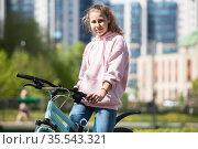 Blond teenage girl sitting on her blue bicycle, portrait outdoor. Стоковое фото, фотограф Кекяляйнен Андрей / Фотобанк Лори