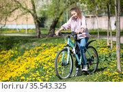 Teenager girl standing with her blue bicycle on pathway with yellow flowers. Стоковое фото, фотограф Кекяляйнен Андрей / Фотобанк Лори