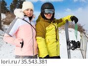 Girl and man in winterwear holding snowboard, looking at camera, winter resort with sunny day. Стоковое фото, фотограф Кекяляйнен Андрей / Фотобанк Лори