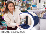 Woman chooses accessories for cats in pet store. Стоковое фото, фотограф Яков Филимонов / Фотобанк Лори