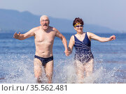 beautiful mature couple runs on the water along the wild beach on a hot summer day. Стоковое фото, фотограф Акиньшин Владимир / Фотобанк Лори