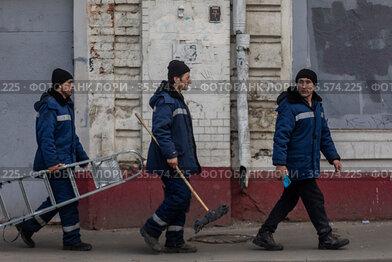 Сотрудники коммунальной службы идут по улице в центре города Москвы, Россия