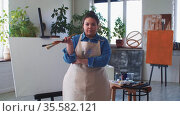 A woman paint artist brings brushes in the studio - posing with brushes in hand and looking in the camera. Стоковое видео, видеограф Константин Шишкин / Фотобанк Лори