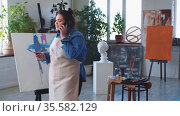 A woman paint artist talking on her phone in the studio in the middle of the drawing process. Стоковое видео, видеограф Константин Шишкин / Фотобанк Лори