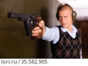 Hand of shooter squeezing pistol grip and pressing trigger at firing range. Стоковое фото, фотограф Яков Филимонов / Фотобанк Лори