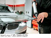 Glazier applying rubber sealing to windshield in garage, close up... Стоковое фото, фотограф Zoonar.com/DAVID HERRAEZ CALZADA / easy Fotostock / Фотобанк Лори