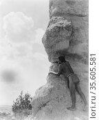 San Ildefonso man peering from behind large rock formation, c1927... Редакционное фото, агентство World History Archive / Фотобанк Лори