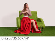 Young woman combing her long straight hair with a comb while sitting on the sofa in the studio. Стоковое фото, фотограф Евгений Харитонов / Фотобанк Лори