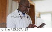 African american senior male doctor wearing white coat writing in notebook. Стоковое видео, агентство Wavebreak Media / Фотобанк Лори