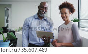 Portrait of smiling diverse businessman and businesswoman, man holding digital tablet. Стоковое видео, агентство Wavebreak Media / Фотобанк Лори