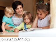 Woman with three children at table reading book. Стоковое фото, фотограф Дарья Филимонова / Фотобанк Лори
