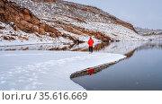 Warmly dressed man is walking or jogging in winter scenery on a shore... Стоковое фото, фотограф Zoonar.com/Marek Uliasz / easy Fotostock / Фотобанк Лори