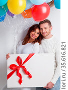 Young smiling couple with balloons and big gift box on white. Стоковое фото, фотограф Zoonar.com/Ivan Mikhaylov / easy Fotostock / Фотобанк Лори