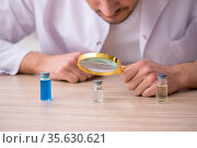 Young male chemist doctor holding vial. Стоковое фото, фотограф Elnur / Фотобанк Лори