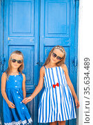 Little happy girls in dresses at street of typical greek traditional village on Mykonos Island, in Greece. Стоковое фото, фотограф Дмитрий Травников / Фотобанк Лори