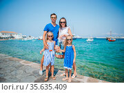 Parents and kids at street of typical greek traditional village on Mykonos Island, in Greece. Стоковое фото, фотограф Дмитрий Травников / Фотобанк Лори