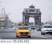 Такси Uber едет по выделенной для общественного транспорта полосе по Кутузовскому проспекту на фоне Триумфальной арки. Редакционное фото, фотограф Сайганов Александр / Фотобанк Лори