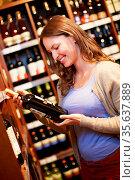 Lächelnde Frau kauft eine Flasche Rotwein im Supermarkt. Стоковое фото, фотограф Zoonar.com/Robert Kneschke / age Fotostock / Фотобанк Лори