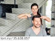 Junges Paar beim Haare selber schneiden mit Schere und Kamm zu Hause. Стоковое фото, фотограф Zoonar.com/Robert Kneschke / age Fotostock / Фотобанк Лори