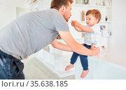 Kleinkind als Sohn gibt seinem Vater einen Keks als Konzept für teilen... Стоковое фото, фотограф Zoonar.com/Robert Kneschke / age Fotostock / Фотобанк Лори