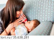 Mutter füttert ihr Baby fürsorglich mit der Milch Flasche auf dem... Стоковое фото, фотограф Zoonar.com/Robert Kneschke / age Fotostock / Фотобанк Лори