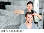 Lächelnde Frau schneidet selber Haare von ihrem Mann mit Kamm und... Стоковое фото, фотограф Zoonar.com/Robert Kneschke / age Fotostock / Фотобанк Лори
