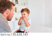 Vater kümmert sich um seinen Sohn mit Keks zu Hause als Konzept für... Стоковое фото, фотограф Zoonar.com/Robert Kneschke / age Fotostock / Фотобанк Лори