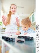 Zwei Kinder bauen eine Strecke aus Dominosteinen auf einem Tisch. Стоковое фото, фотограф Zoonar.com/Robert Kneschke / age Fotostock / Фотобанк Лори