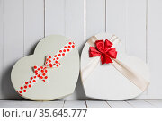 Two Heart shape boxes with red ribbons and bows on white wooden background... Стоковое фото, фотограф Zoonar.com/Ivan Mikhaylov / easy Fotostock / Фотобанк Лори