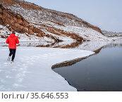 Warmly dressed man is jogging in winter scenery on a shore of mountain... Стоковое фото, фотограф Zoonar.com/Marek Uliasz / easy Fotostock / Фотобанк Лори