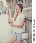 Girl leaning against edifice using phone to find address. Стоковое фото, фотограф Яков Филимонов / Фотобанк Лори
