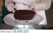 the chef cuts the top of the biscuit to get a smooth shell of chocolate cake. Стоковое видео, видеограф Ирина Мойсеева / Фотобанк Лори