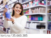 Positive young woman looking for haircare products at shop. Стоковое фото, фотограф Татьяна Яцевич / Фотобанк Лори