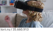 Caucasian boy gesturing while using vr headset sitting on the couch at home. Стоковое видео, агентство Wavebreak Media / Фотобанк Лори